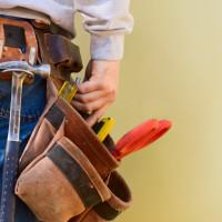 A young construction worker reaches into his tool belt. Copy Space.